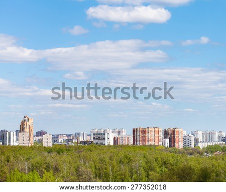 blue sky with white clouds over city and green forest in sunny spring day - stock photo