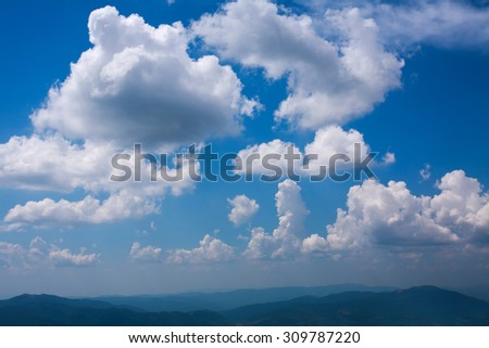 Blue sky with white clouds over the mountain hills