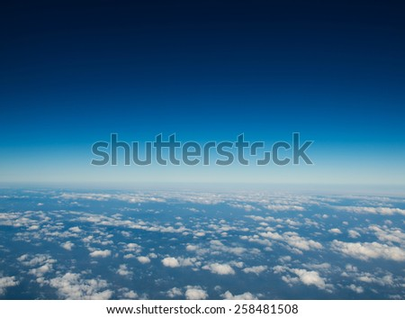 Blue sky with white clouds, view from a flying airplane. - stock photo