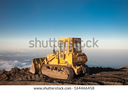 Blue sky with Yellow tractor at the top of the Etna mountain with view on the clouds and the valley - stock photo