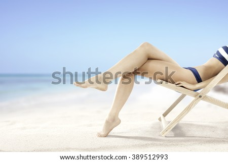 blue sky yellow sand of beach and legs and chair