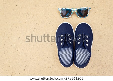 Blue sneakers and sunglasses. Summer holidays. Top view trendy shoes and glasses. Hipster set. Children theme. Space for text - stock photo