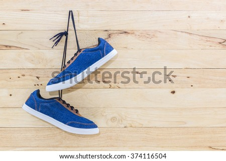Blue sneakers hang on a nail on a brown wooden wall. Canvas Shoe. - stock photo