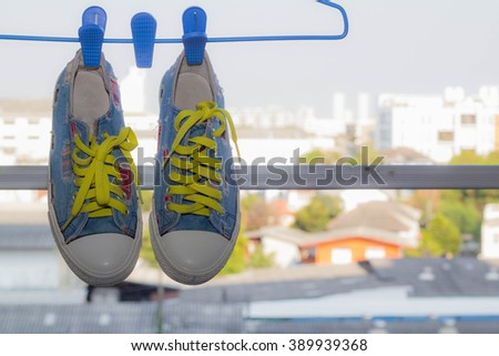 Blue sneakers hanging on the clothesline - stock photo