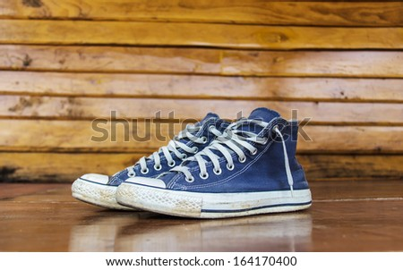 Blue sneakers on the wooden floor  - stock photo