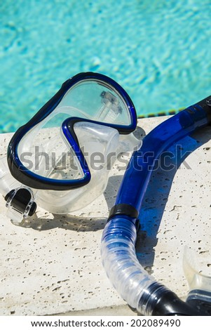 Blue snorkel resting on diving mask by a pool/Snorkel Gear/Snorkel equipment near a pool  - stock photo
