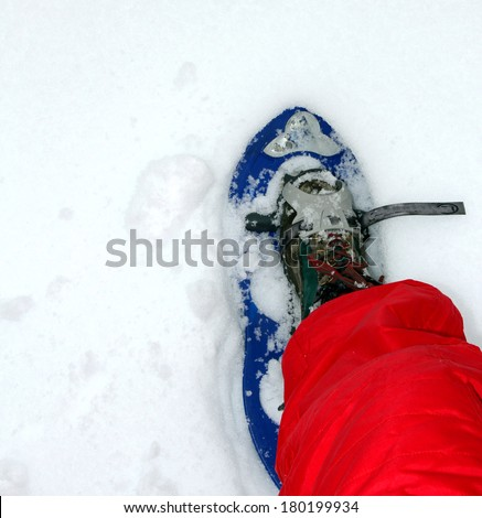 blue snow shoes for walking on soft snow mountain with red snow suit - stock photo