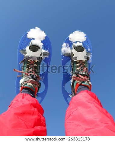 blue Snowshoes and Red Ski suit in winter - stock photo