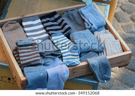 blue sock in wood tray ,woman's sock and pile of clothes in open drawer, warm winter ,mismatched socks sits on a table waiting to be matched and put away.  it look overwhelming, cloth shop