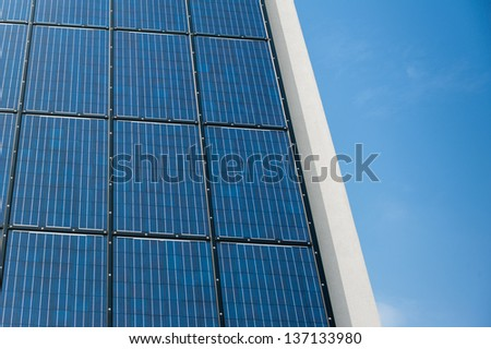 Blue solar cell panel on a wall reflecting the sun and the cloudless blue sky - stock photo