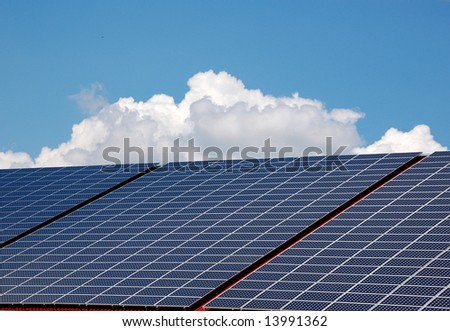 Blue solar energy panels on a roof with sky and clouds