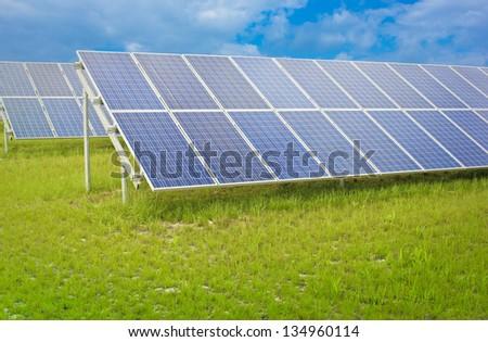 blue solar panels in a green field - stock photo
