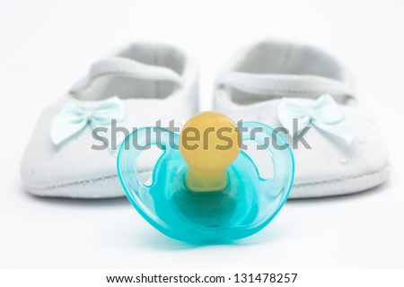 Blue soother with baby booties on white background