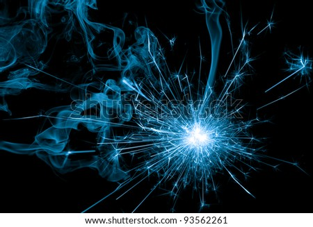 blue sparkler and smoke on black background - stock photo