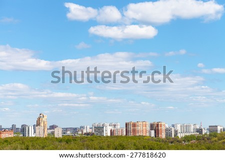 blue spring sky with white clouds over city and green woods in sunny day - stock photo