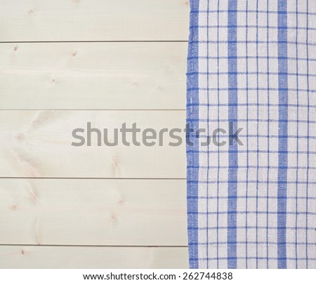 Blue squared tablecloth or towel over the surface of a wooden table - stock photo