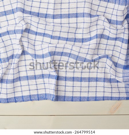 Blue squared tablecloth or towel over the surface of a wooden table