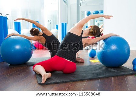 Blue stability ball in women Pilates class rear mirror view