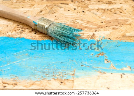 blue stain being applied to new wooden board on outdoor deck - stock photo