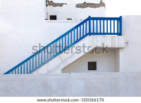 blue stairs with handrails  with white stucco wall in background.