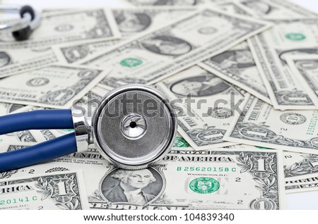 blue Stethoscope and dollars illustrating expensive healthcare - stock photo