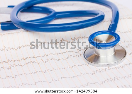 Blue stethoscope laying on ECG results close up - stock photo