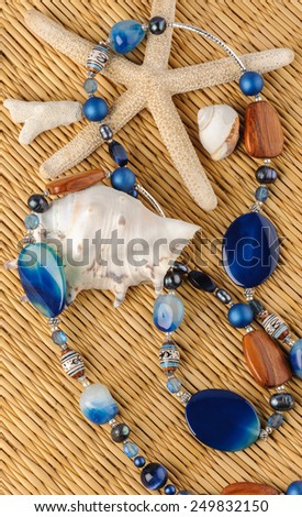 Blue stones necklace lying on straw background - stock photo