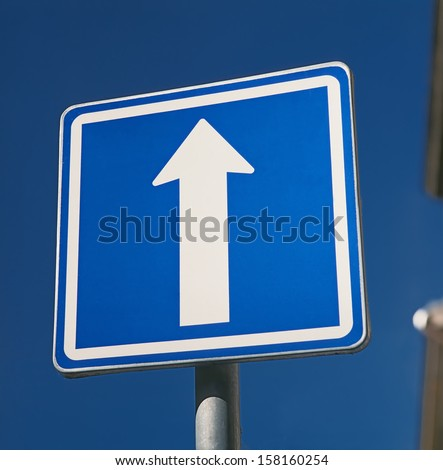 blue strait direction road sign against blue sky - stock photo