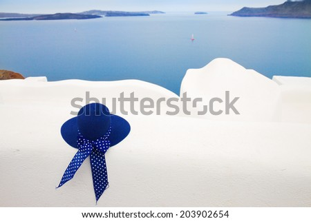 blue straw sun hat against volcano caldera, beautiful details of Santorini island, Greece - stock photo
