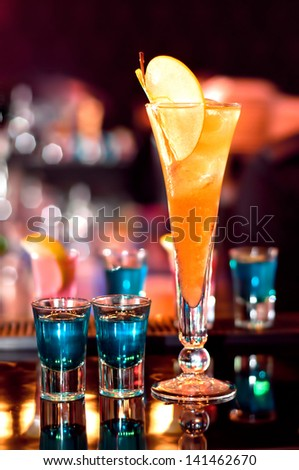 blue, strong alcoholic drink in small glasses and an appletini on bar waiting to be served - stock photo