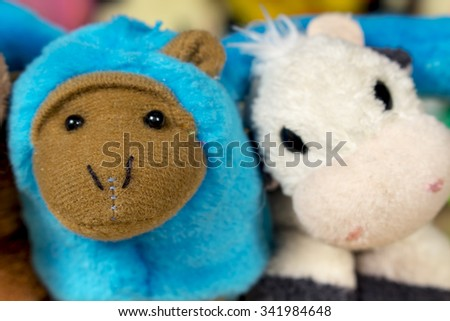 Blue stuffed monkey embraced with teddy cow. Friendship.