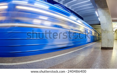 Blue subway train in motion at the underground station. Wide angle - stock photo