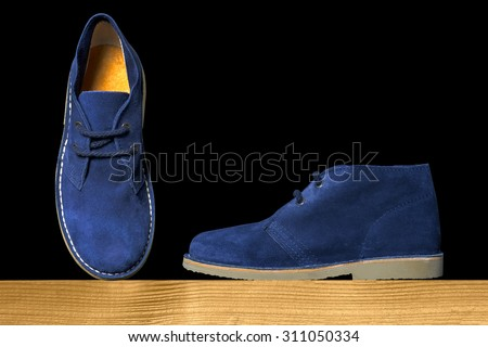 blue suede boots on a wooden shelf over a black background - stock photo