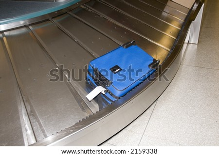 BLue suitcase at airport - stock photo