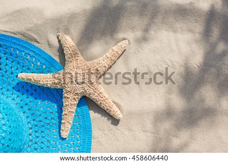 blue sun hat with a starfish on the sand on the beach, the concept of vacation, leisure, travel