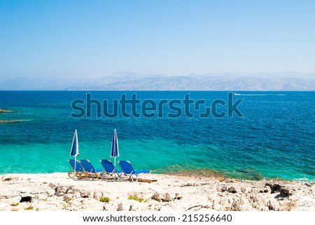 Blue sunbeds and blue-white parasols (umbrellas) on a beautiful rocky beach. - stock photo