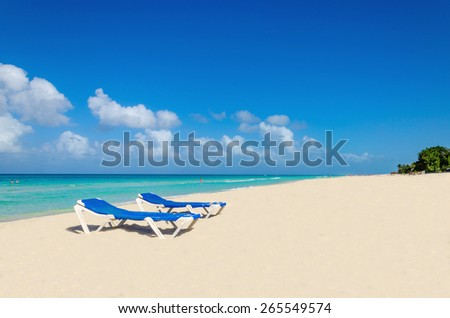 Blue sunbeds on sandy Caribbean beach against blue sky and azure water, islands of Central America - stock photo