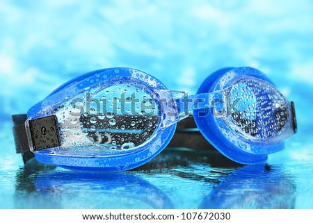 blue swim goggles with drops on blue sea background - stock photo