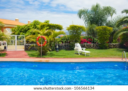 blue swimming pool in exotic tropical garden - stock photo