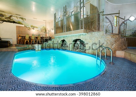 Blue swimming pool in modern spa interior. Resort and wellness. Blue clear water indoor pool in spa center. Healthcare and rest, relaxation concept.  - stock photo