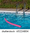 Blue Swimming Pool. Ladder, and Pink Pool Toy in Full Sunlight - stock photo