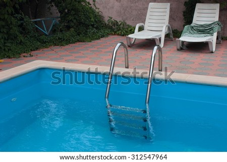 blue swimming pool with a ladder and chairs beside it
