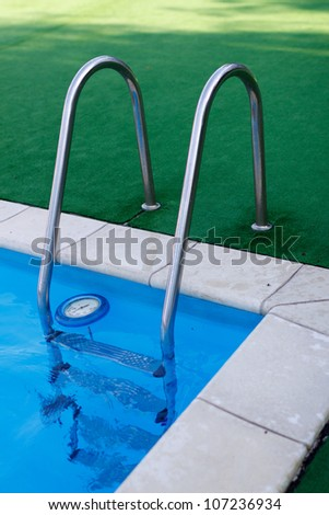 blue swimming pool with stair at hotel close up - stock photo
