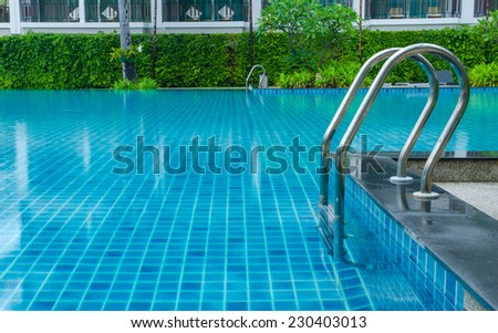 blue swimming pool with staircase at hotel.