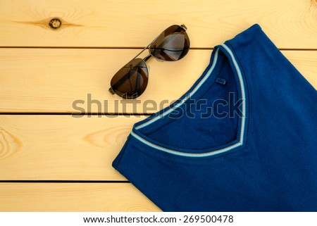 Blue t-shirt with sunglasses on wooden board - stock photo