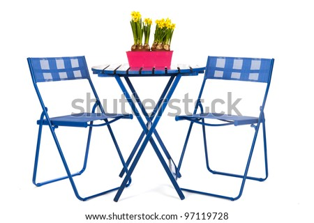 Blue table and chairs with spring daffodills