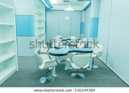 blue tables and white chairs in the empty modern library