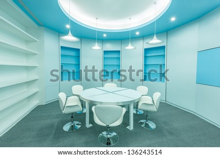 blue tables and white chairs under white ceiling lamps in the empty modern library - stock photo