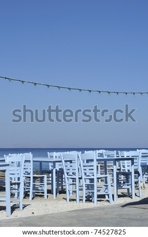 Blue tables & chairs on the seafront in Mykonos Town Greece. - stock photo