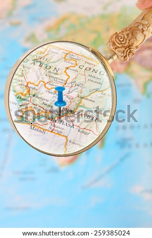 Blue tack on map of Africa with magnifying glass looking in on Kinshasa, Democratic Republic of Congo - stock photo